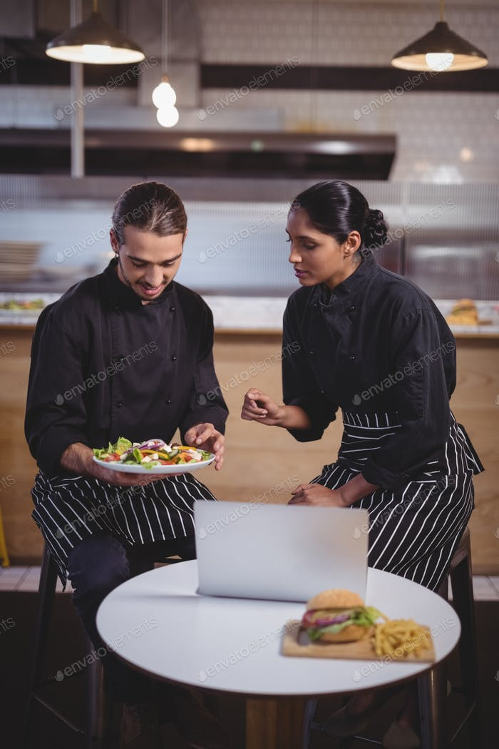 Young wait staff discussing over food while sitting at coffee shop