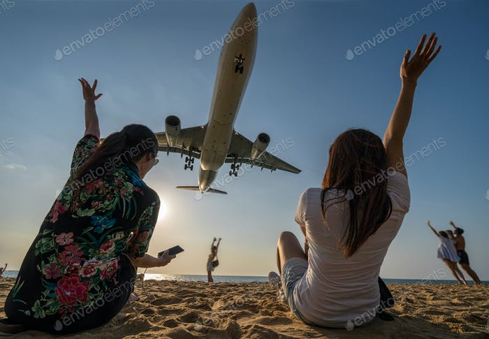 Scene of Two traveler woman showing hand and funning with Airplane landing closely