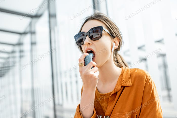 Asthmatic woman using inhaler outdoors