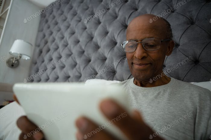 Senior man using digital tablet while relaxing on bed