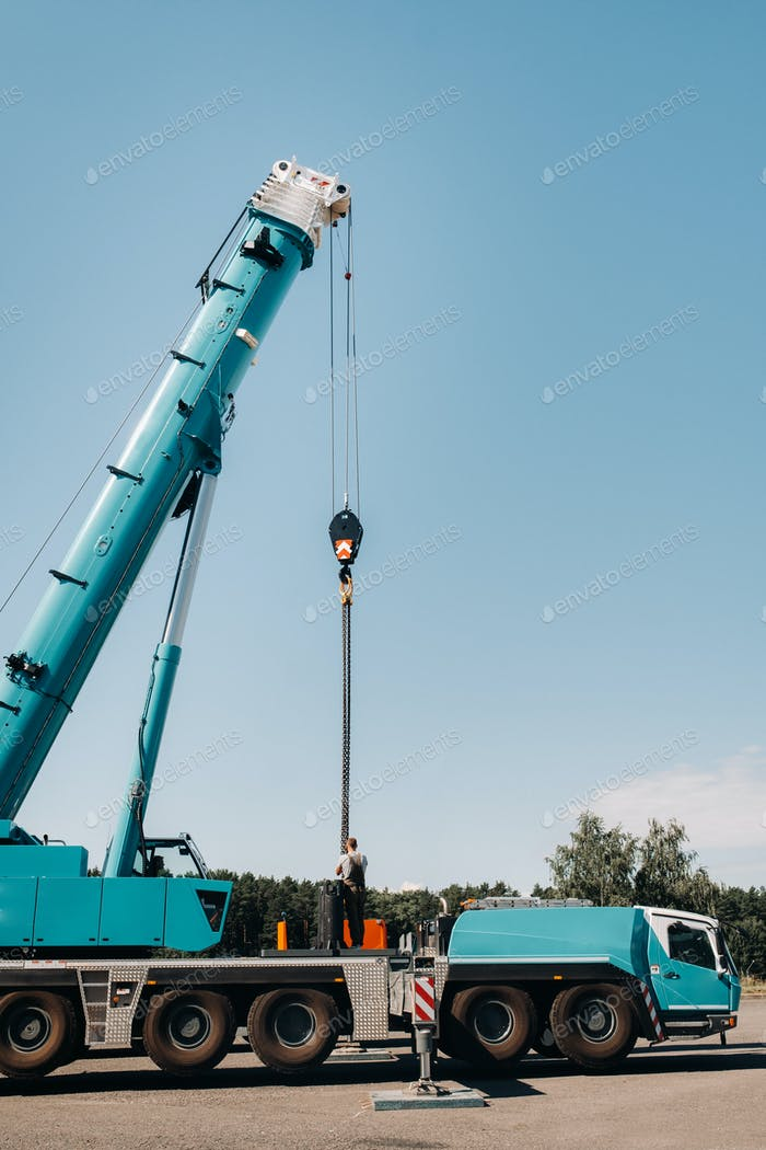 the counterweight is installed by an unrecognizable worker on a large blue car crane and is prepared