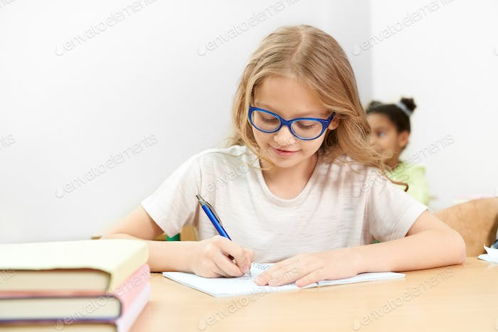 Front view of studious girl doing task on lesson in school