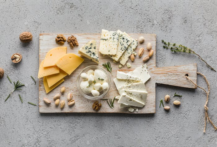 Assortment of cheese with nuts on wooden board