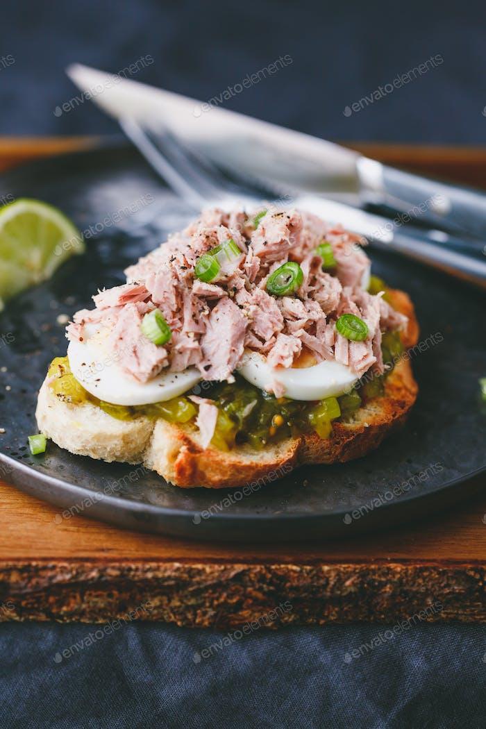 Offenes Sandwich mit Dosen-Tunfisch, Ei und eingelegtem Gurkendressing serviert mit Limette.