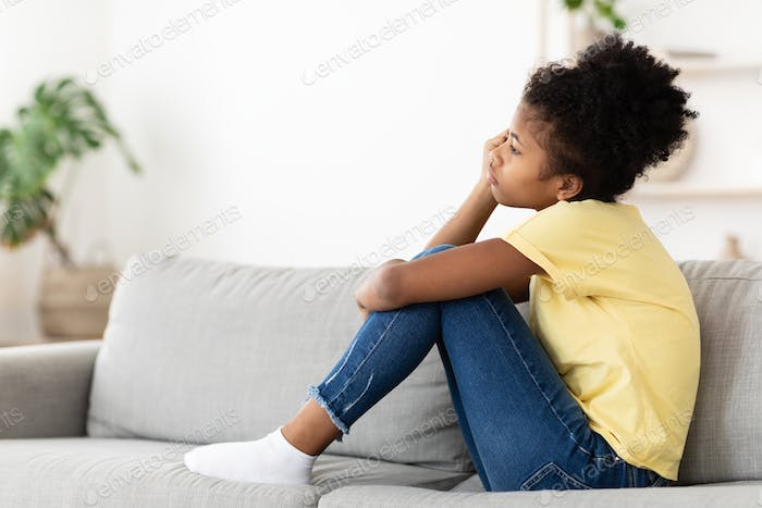 Unhappy Black Kid Girl Sitting On Couch At Home Alone