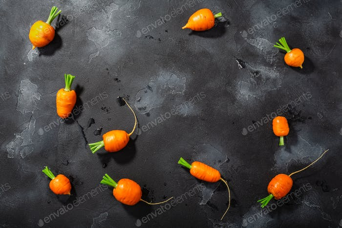 Short Rondo carrots on dark textured background with copy space,  top view