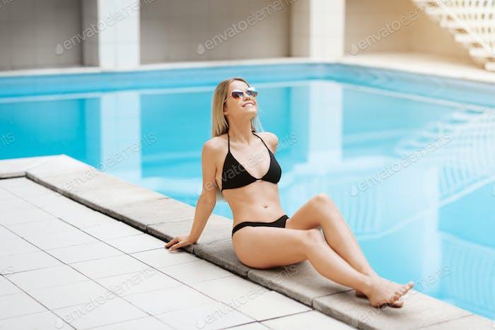 Sexy junge Dame sitzt in der Nähe von Schwimmbad im tropischen Resort, Freiraum