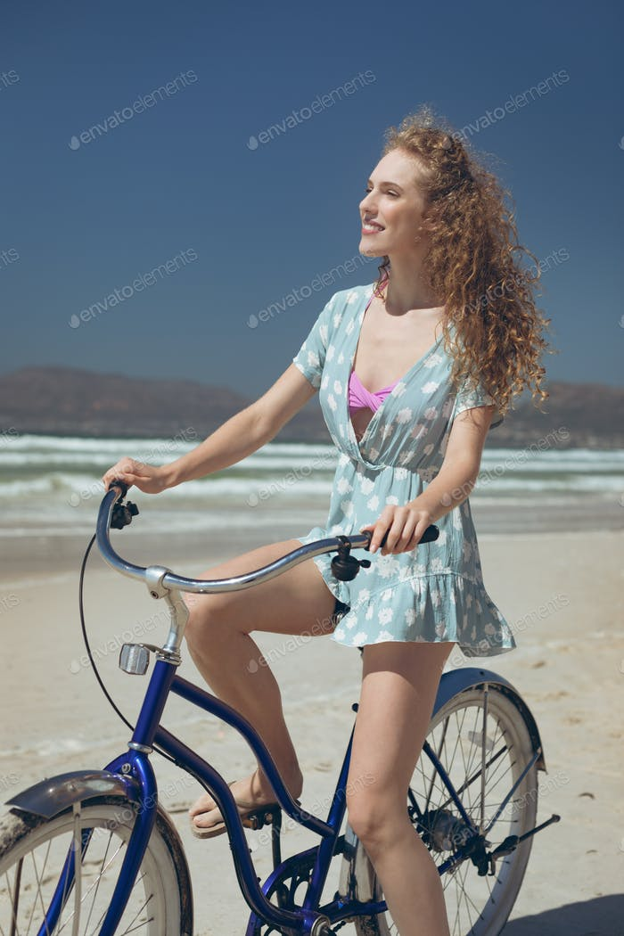 Side view of Caucasian woman riding bicycle at beach on a sunny day.She is smiling