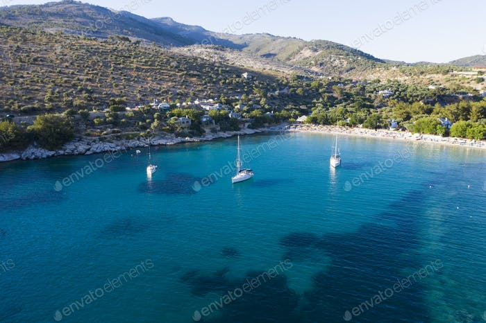 Sail boats in turquoise water in Thassos, Greece