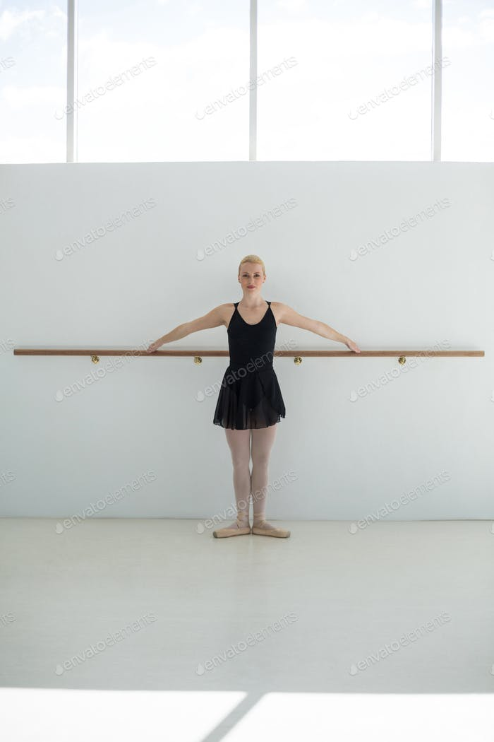 Ballerina practicing ballet moves at barre