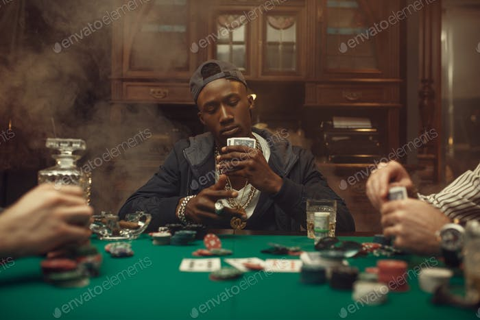 Poker players at gaming table with bets, casino