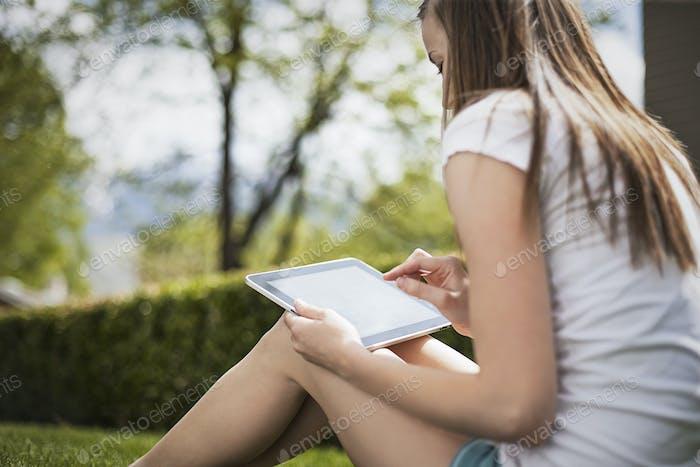Ein Mädchen, das auf dem Rasen sitzt, mit einem elektronisch Handgerät, liest.