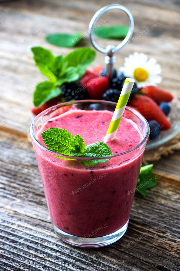 Summer  berries smoothie on rustic wooden background