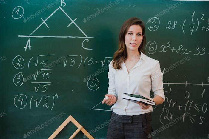 Junge attraktive weibliche Lehrerin der Mathematik interagieren mit ihren jungen Grundschülern fragen eine