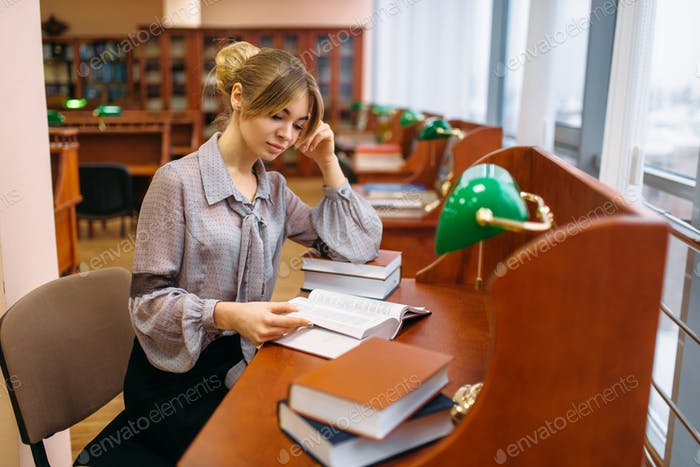 Woman reading at the table in university library
