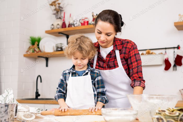 Young woman in apron standing close to her little son rolling homemade dough