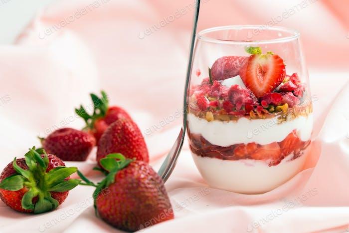 Strawberry yogurt with muesli on pink background