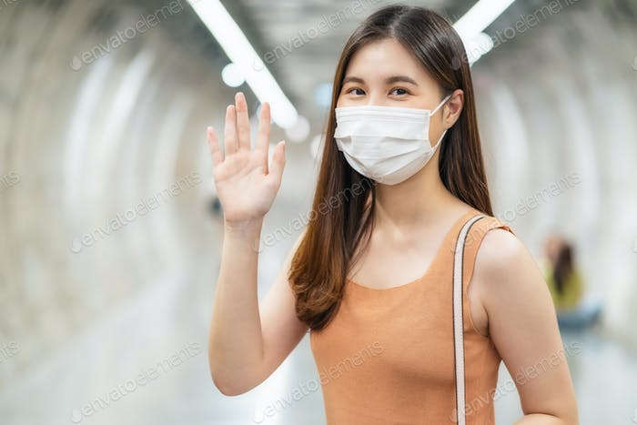Young Asian woman passenger wearing surgical mask and looking at camera to hello