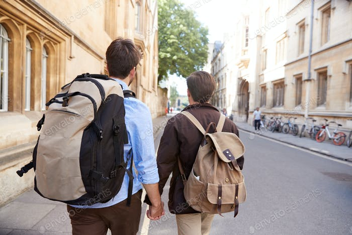 Rear View Of Male Gay Couple On Vacation Wearing Backpacks Holding Hands Walking Along City Street