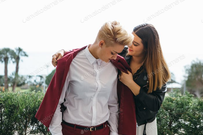 Careful woman covering girlfriend with coat