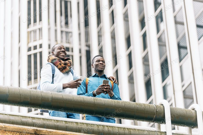 Hommes d'affaires utilisant mobile dans la rue.