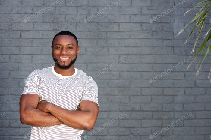 lächelnd gutaussehender Mann stehend mit Armen gekreuzt