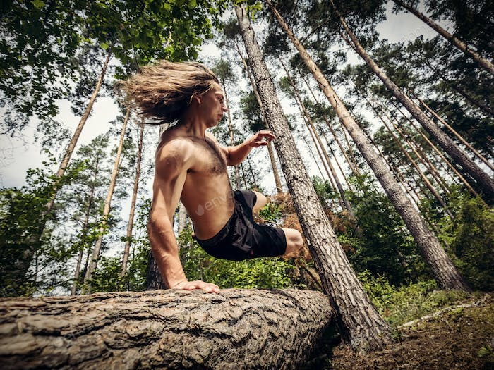 Young man jumping over a tree trunk in the forest.