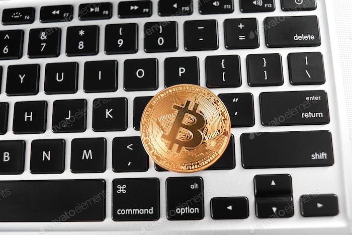 One golden bitcoin as world main cryptocurrency placed on laptop keyboard