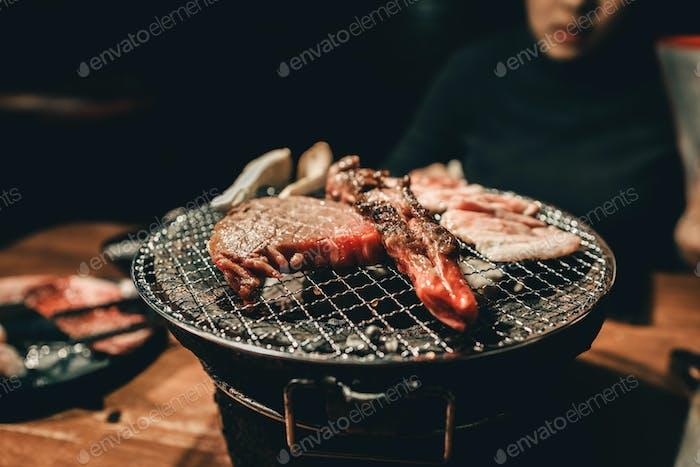 Schließen Sie Schweinefleisch auf einem Holzkohlegrill im Restaurant.