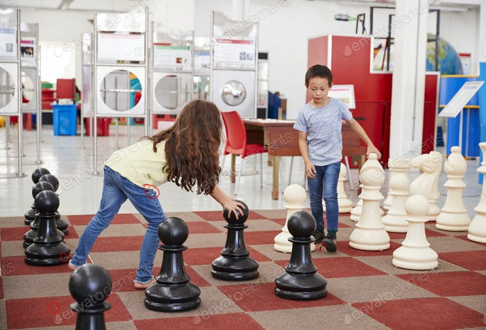 Schoolchildren playing giant chess at a science centre