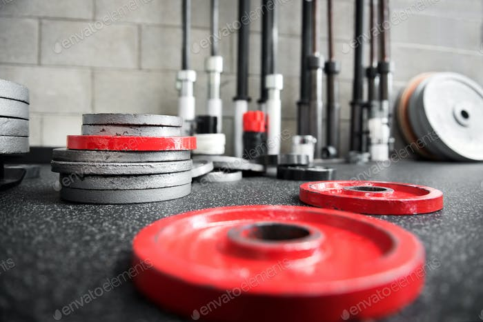 Scattered barbell weights on the floor of a gym