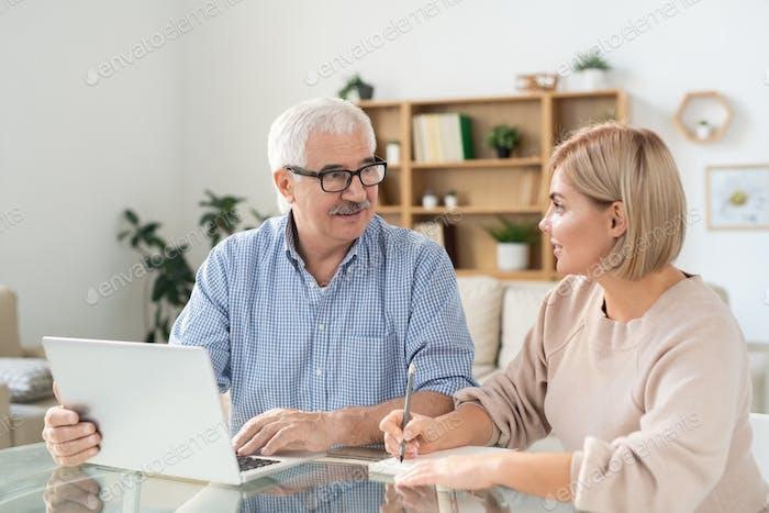Junge Frau macht Notizen im Notizblock während der Blick auf ältere Vater mit Laptop