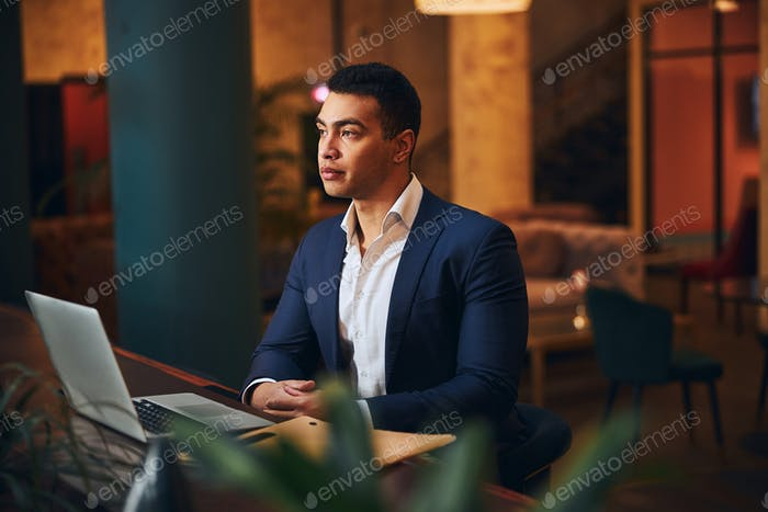 Hombre guapo tranquilo sentado en un espacio de coworking
