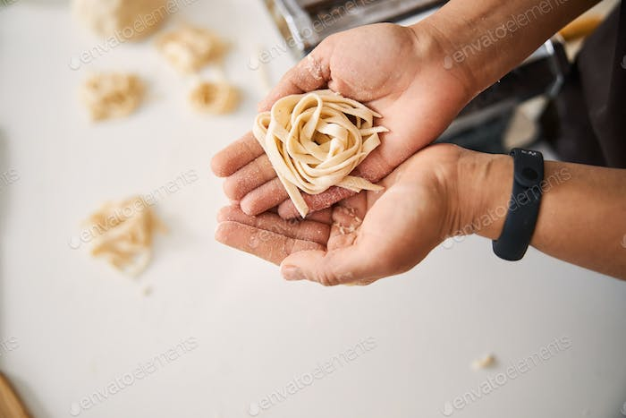 Person holding stripes of dough in two hands