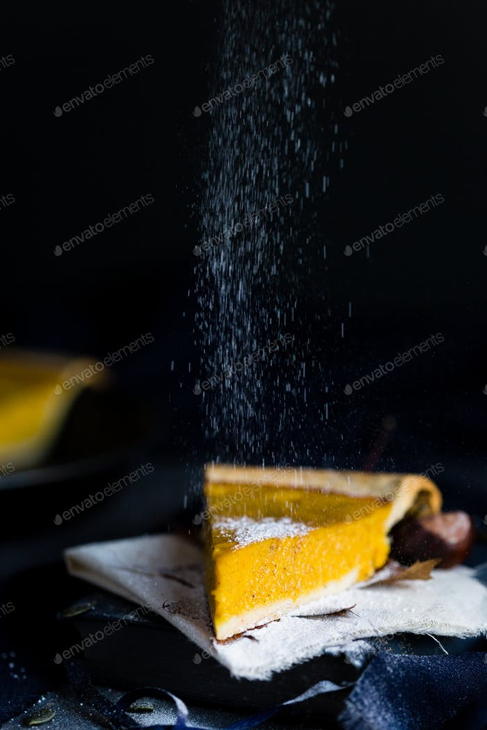Sprinkling Icing Sugar on a Slice of Pumpkin Pie