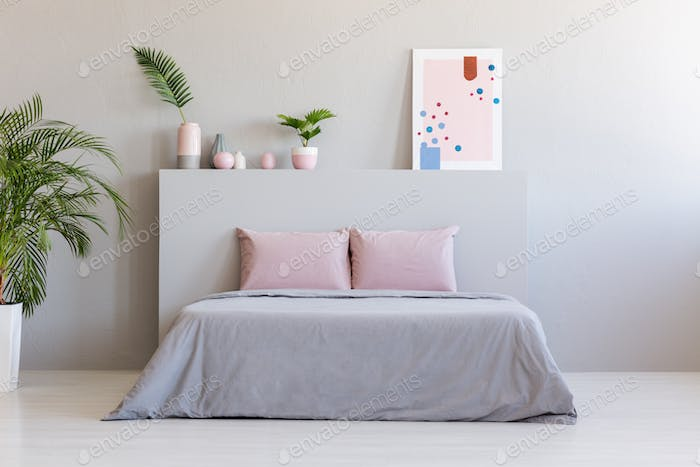 Poster and plants on bedhead of bed with pink cushions in grey b