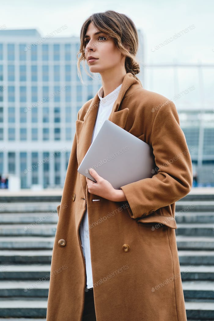Young attractive stylish businesswoman in coat with laptop confidently looking away on city street