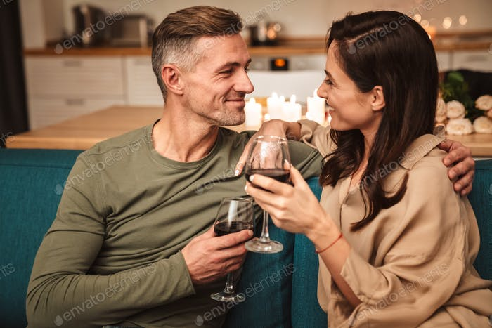 Image of couple drinking red wine while having romantic dinner at home