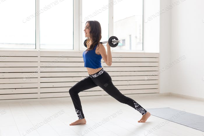 Fitness, sport and people concept - smiling sporty woman with barbell doing split squat or lunge