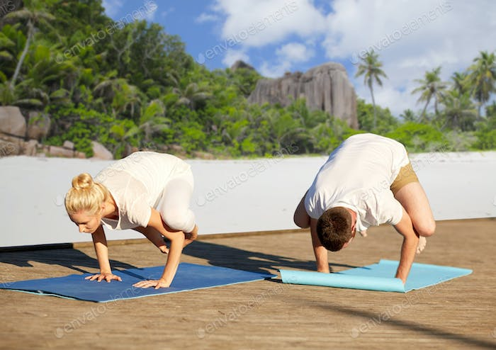 couple making yoga crow pose over tropical beach