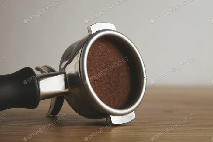 Close up portafilter with coffee isolated wooden table