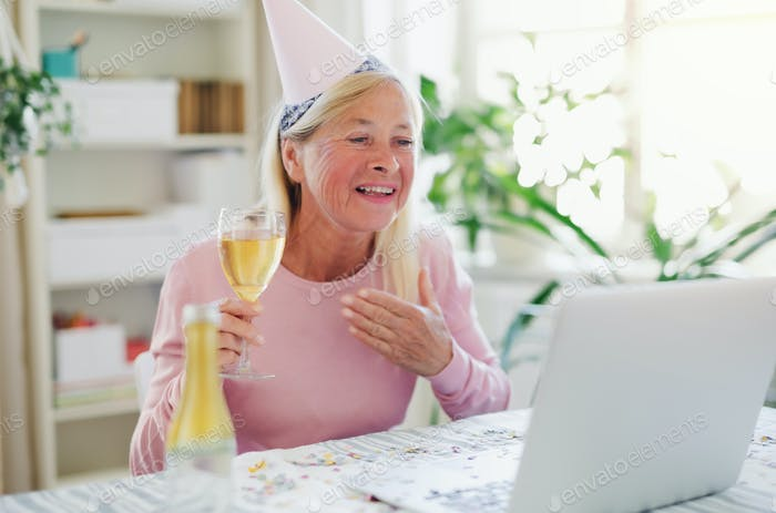 Senior woman with laptop indoors at home, celebrating distance birthday