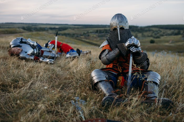 Medieval knight in armor sitting on the ground