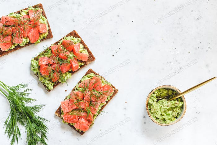 Three toasts with avocado, rye bread, smoked salmon