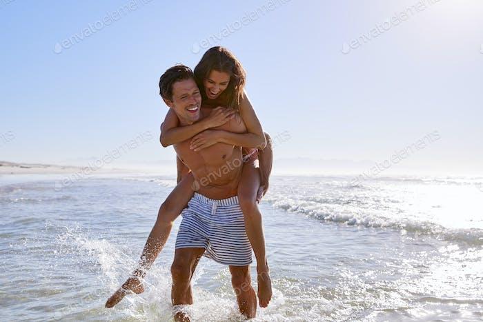 Man Giving Woman Piggyback On Summer Beach Vacation