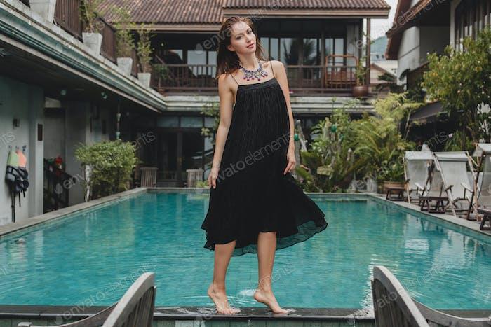 stylish attractive woman in elegant long black dress posing at pool barefoot