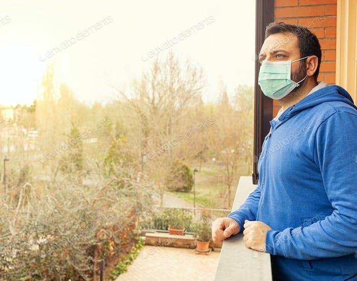 Junger kaukasischer Mann mit Maske und blickt auf die Terrasse