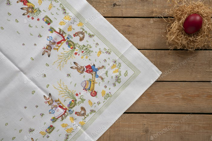 Easter background with an easter tablecloth and a nest with an egg