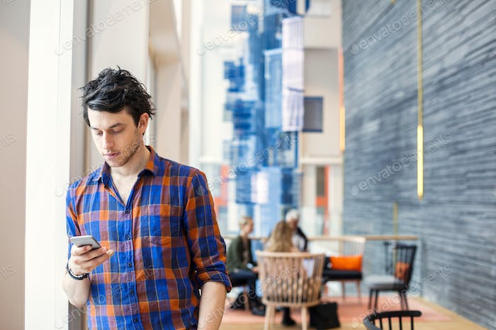 Businessman text messaging through smart phone at hotel lobby