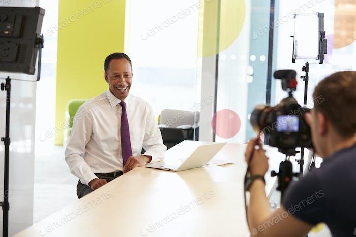 Kameramann und Geschäftsmann mittleren Alters machen Unternehmens- Video